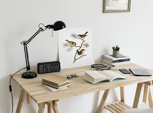 A wooden desk with office supplies and a lamp on it.